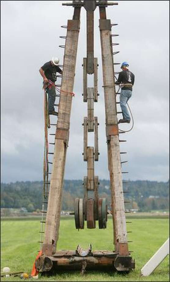 "Two team members of ""The Trebarbarric"" trebuchet team prepare for another hurl. Photo: Brad Vest, Seattle Post-Intelligencer"