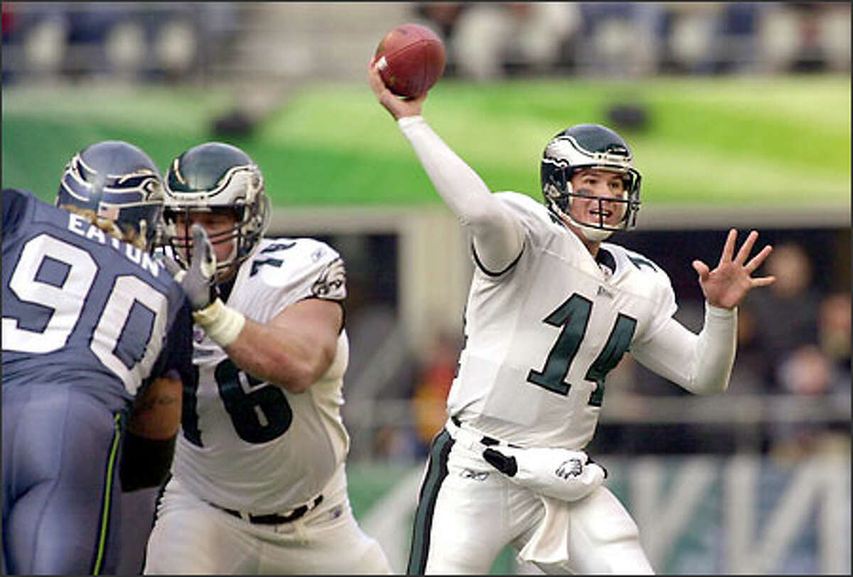 Eagles quarterback A.J. Feeley throws as teammate John Welbourn blocks Seattle's Chad Eaton during the first half at Seahawks Stadium.