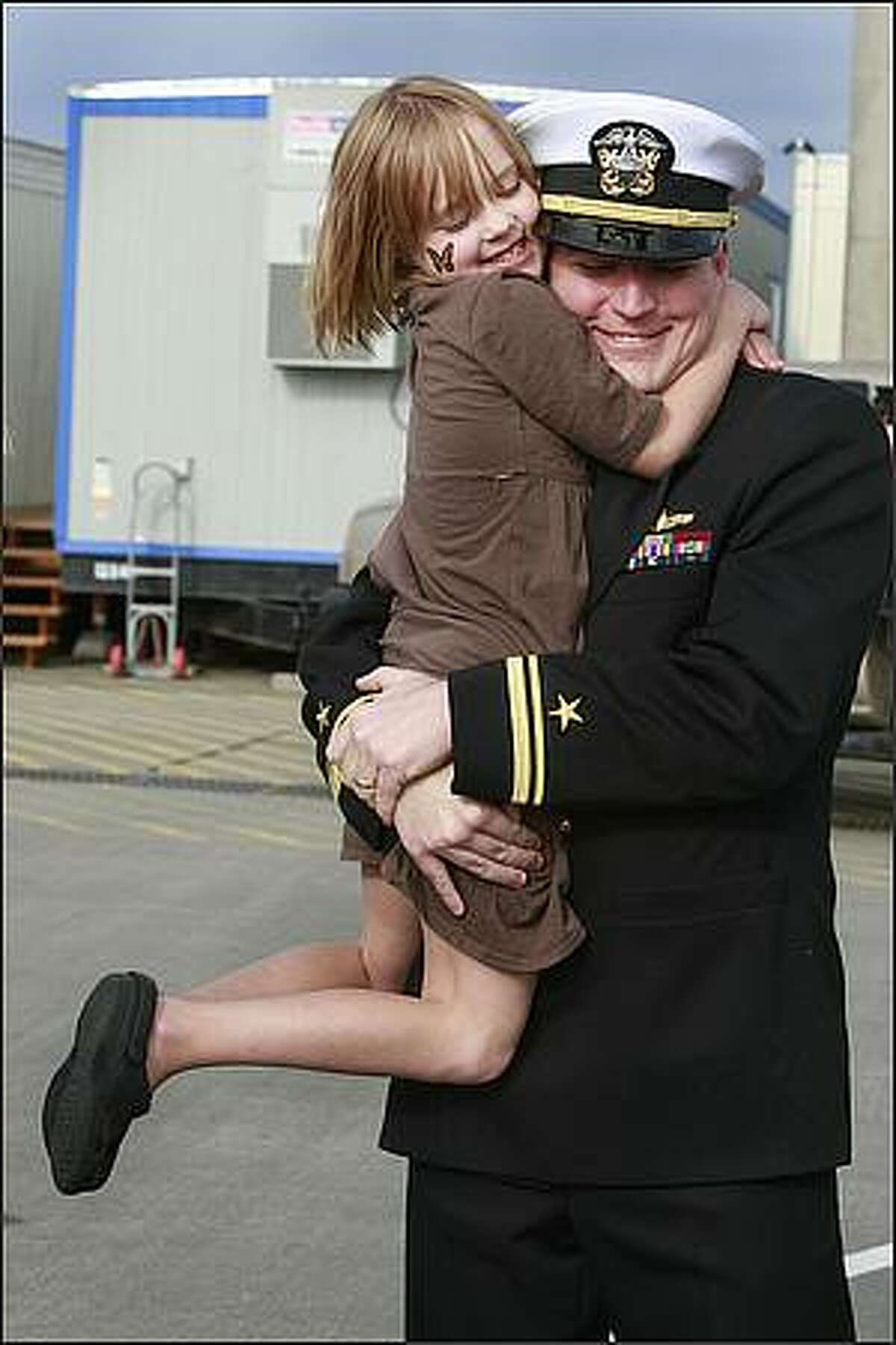 Colleen Huchton, 6, hugs her dad, LTjg Scott Huchton as he arrives home after a seven month deployment on the USS Abraham Lincoln.