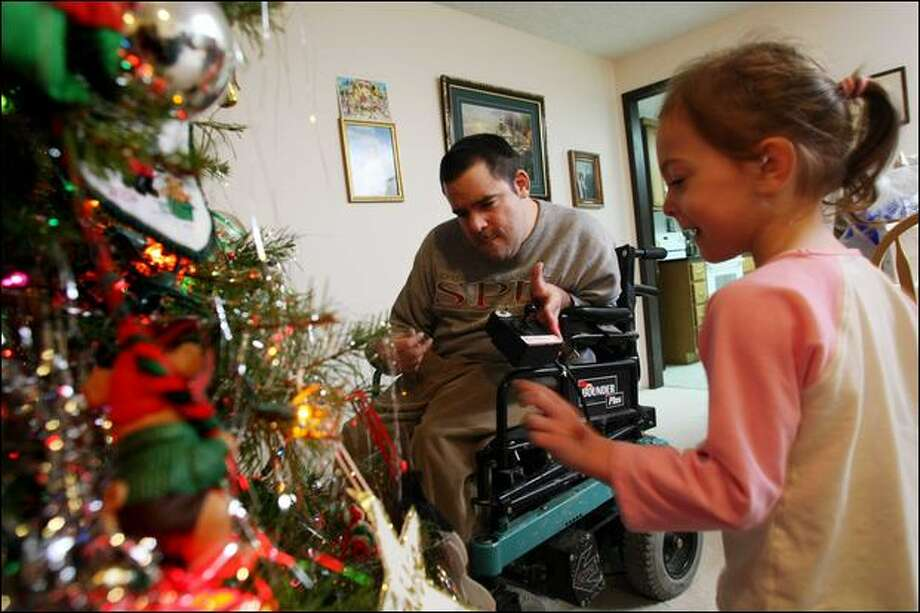 Gabriella Berg, 4, and her father, Kevin, who has cerebral palsy, decorate their Christmas tree in the Auburn home that Parkview Services helped the Berg family buy. Photo: Karen Ducey/Seattle Post-Intelligencer