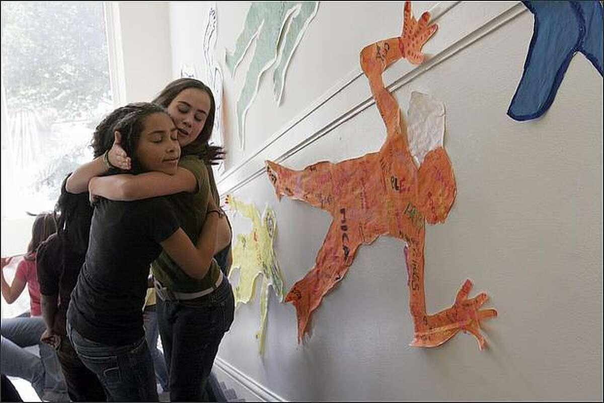 Eighth-grade students Tessa Tweet, left, and Jamie Keene hug in the stairway of Lake Washington Girls Middle School.