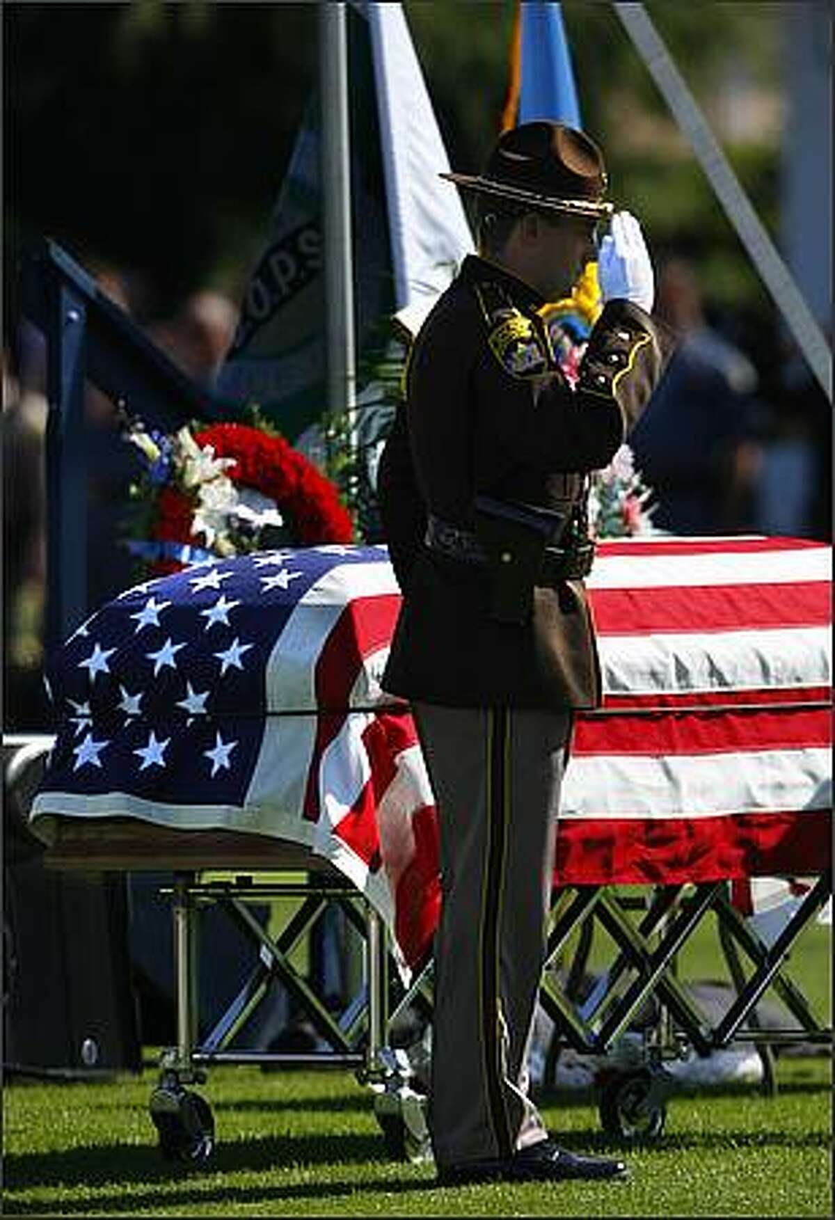 A Skagit County Sheriff Office representative salutes the coffin of Deputy Anne Jackson.