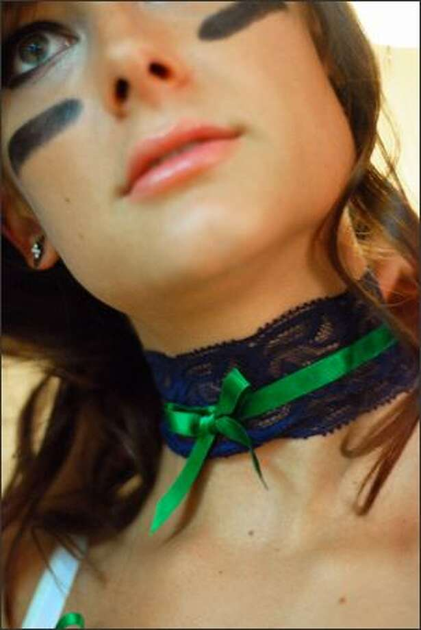 Jenna Bloczynski puts her lace choker on before the Mist photo shoot. These chokers are part of the team's uniform. Photo: Jennifer Au, Seattle Post-Intelligencer