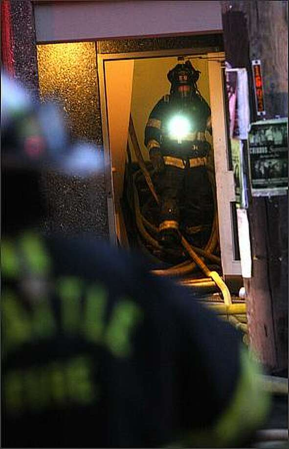 Firefighters work at the scene of an apartment fire at 1605 Bellevue Ave. in Seattle. Photo: Mike Kane, Seattle Post-Intelligencer