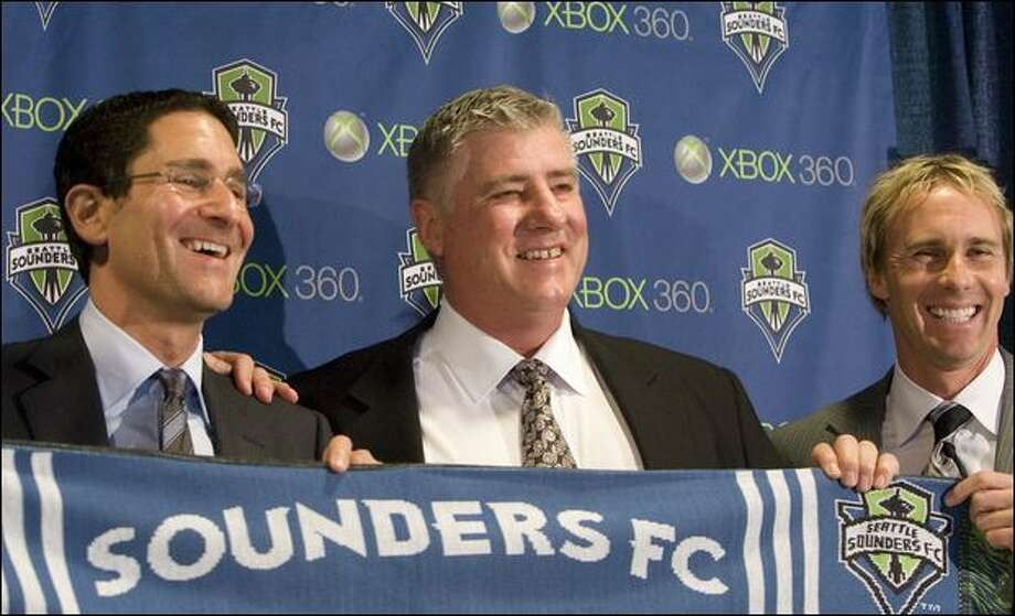 Sounders FC general manager Adrian Hanauer, left, and technical director Chris Henderson, right, pose with new coach Sigi Schmid and a team scarf Tuesday.
