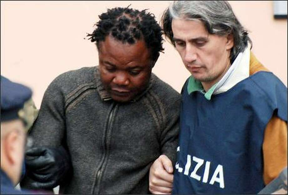 Congolese musician Patrick Diya Lumumba, 37, who owned a bar in Perugia where Amanda Knox worked, is escorted Tuesday from the police station in Perugia. Photo: Getty Images