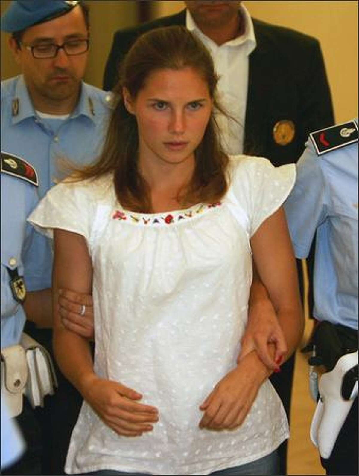One of the three suspects in the murder of British student Meredith Kercher, Amanda Knox, is escorted by police upon her arrival at a court hearing in Perugia on Sept. 16.