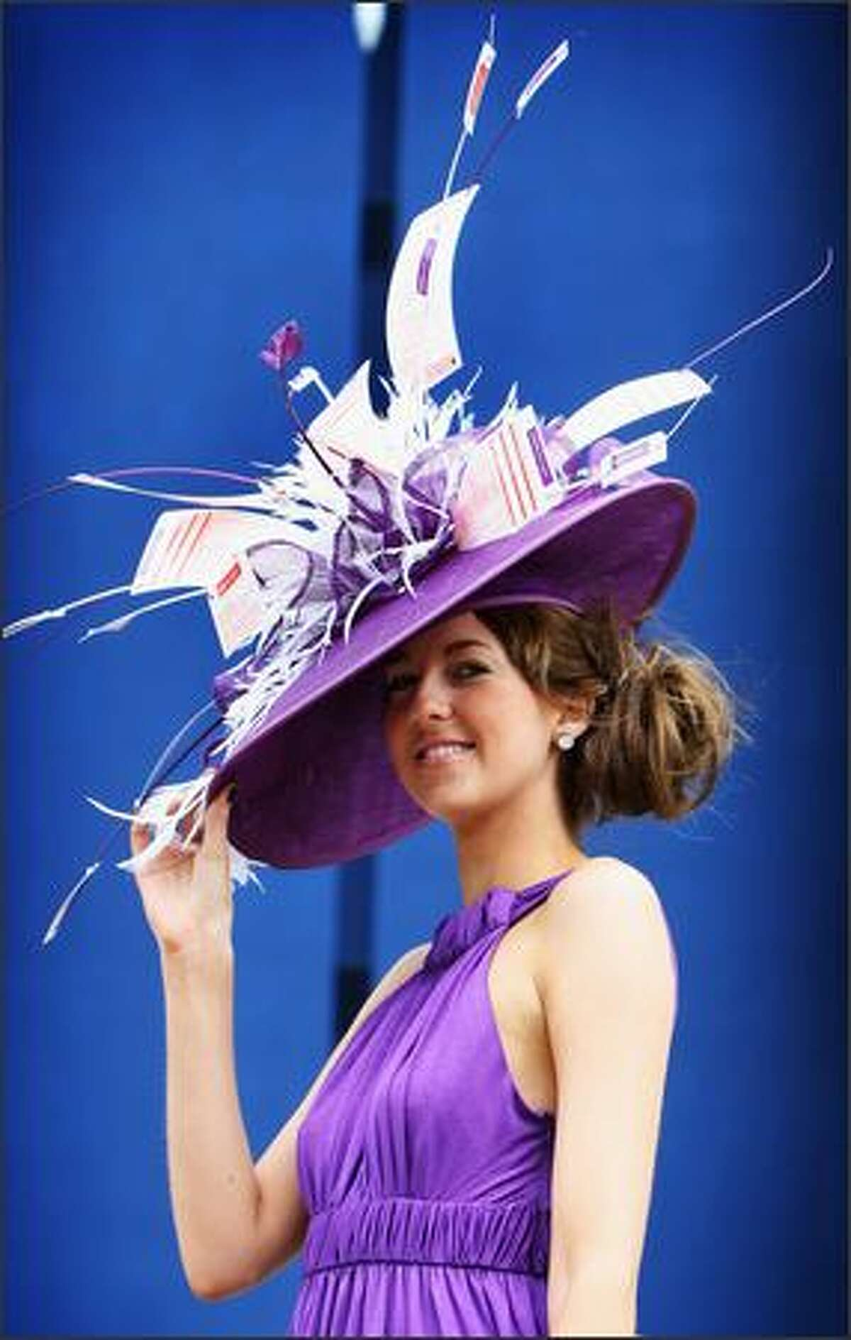A girl in an elaborate hat poses for a photograph as she arrives for the first day of the Royal Ascot horse race meeting in Ascot, England.