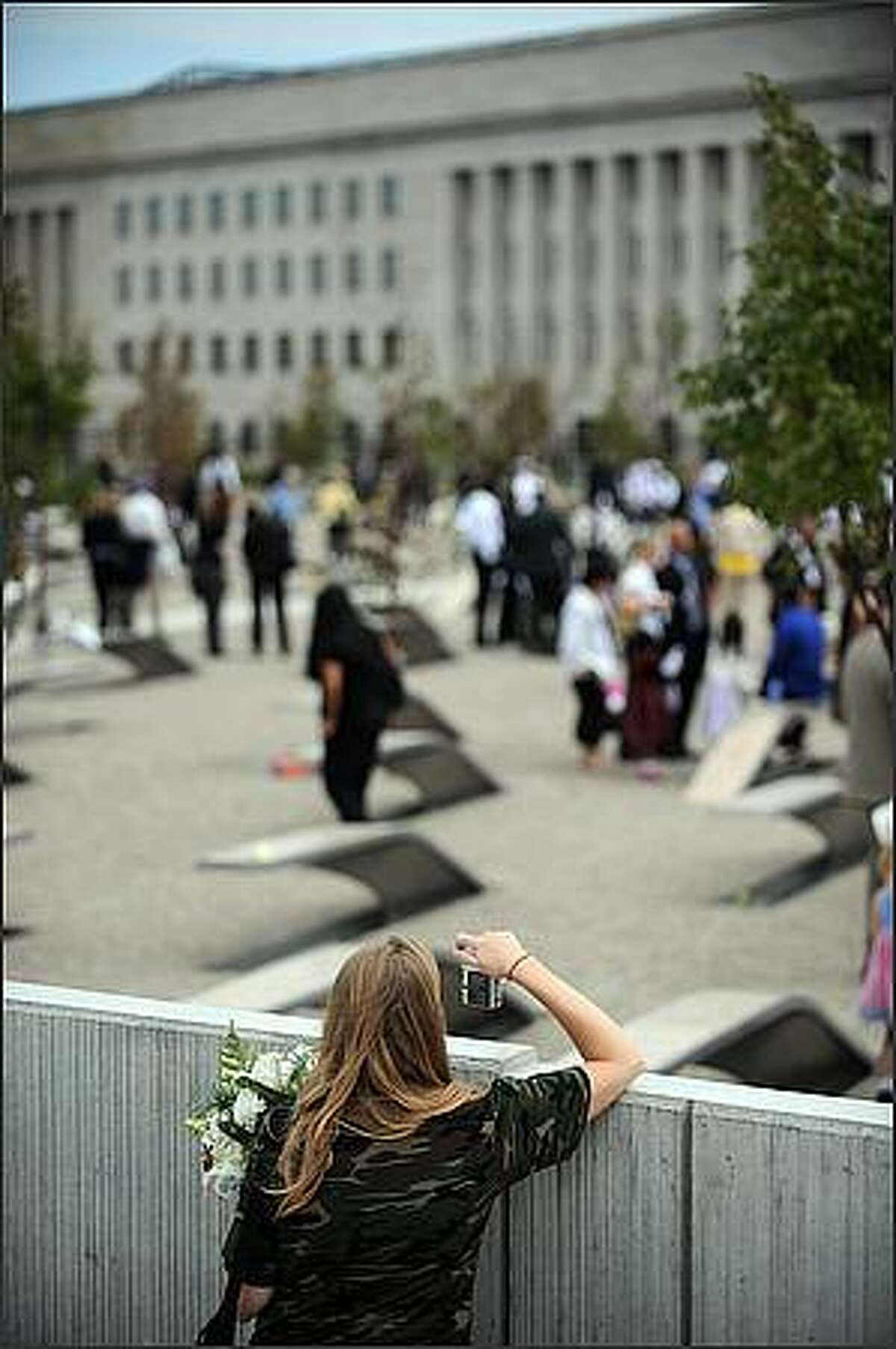 A woman photographs family members as they enter the memorial park after US President George W. Bush officially dedicated the Pentagon Memorial on September 11, 2008 at the Pentagon in Washington, DC. Thousands gathered to dedicate the first September 11 memorial Thursday, observing a moment of silence at the instant seven years ago when an airliner slammed into the Pentagon, killing 184 people and five hijackers. A sailor rang a bell for each of the victims of the attack on the Pentagon, which followed strikes by airliners commandeered by Al-Qaeda suicide squads on the World Trade Center in New York. A fourth hijacked plane crashed in a field in Pennsylvania. AFP PHOTO / TIM SLOAN (Photo credit should read TIM SLOAN/AFP/Getty Images)