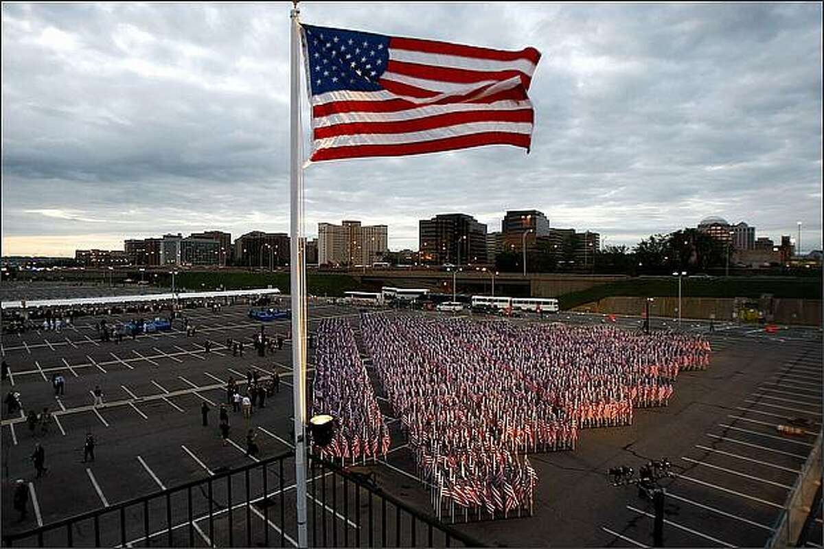 """Nearly 3000 United States flags that make up the """"Healing Field"""" stand in the parking lot outside the Pentagon during the dedication of the Pentagon Memorial September 11, 2008 in Arlington, Virginia. U.S. President George W. Bush will dedicate the memorial, made up of 184 """"memorial units"""" each dedicated to an individual victim killed at the Pentagon when American Airlines Flight 77 slammed into the Department of Defense's headquarters. (Photo by Chip Somodevilla/Getty Images)"""