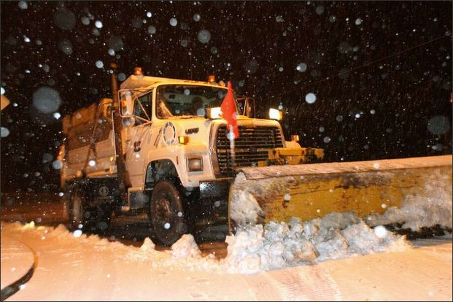 A snowplow from the City of Brier clears the road as snow falls on Tuesday north of Seattle. Some cities in the region were hit by snow Wednesday but  Seattle was spared -- at least for a day Photo: Karen Ducey/Seattle Post-Intelligencer