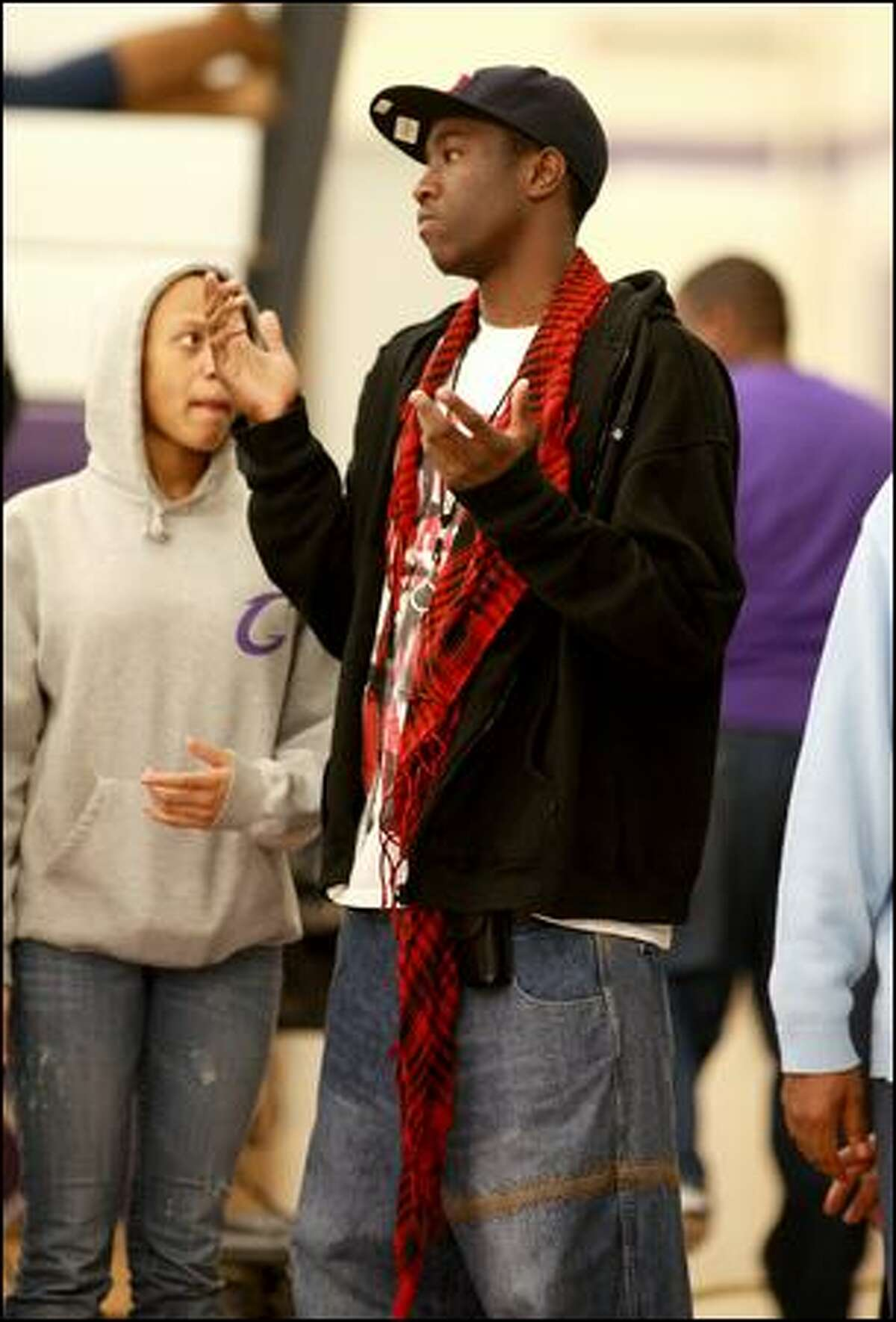 Tony Wroten Jr. talks to supporters at the Garfield-Issaquah game Friday. Wroten hasn't played this season.