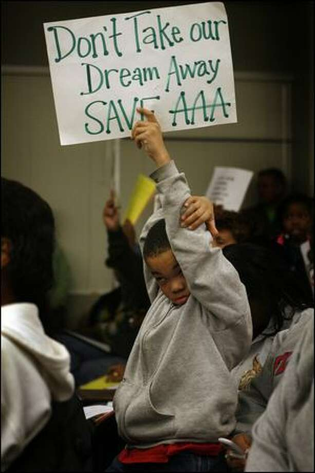 DeTreon Jack, 8, a third-grader at the African American Academy, holds a sign in support of the school during Wednesday's meeting of the Seattle School Board. The district faces a projected $37.1 million budget deficit. Photo: Mike Urban/Seattle Post-Intelligencer