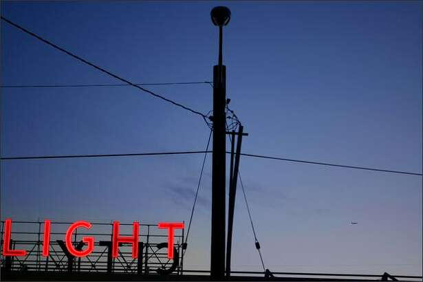 An unlit street light is shown in front of the Seattle City Light building with its signature red neon sign in SODO.