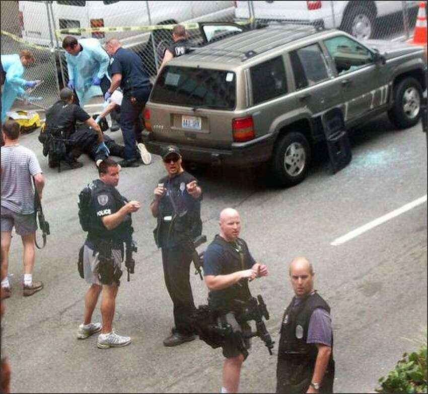 Paramedics attend to a subject (back left) who was shot by police and pulled from the Jeep shown. (Photo by Michele DeMaris)