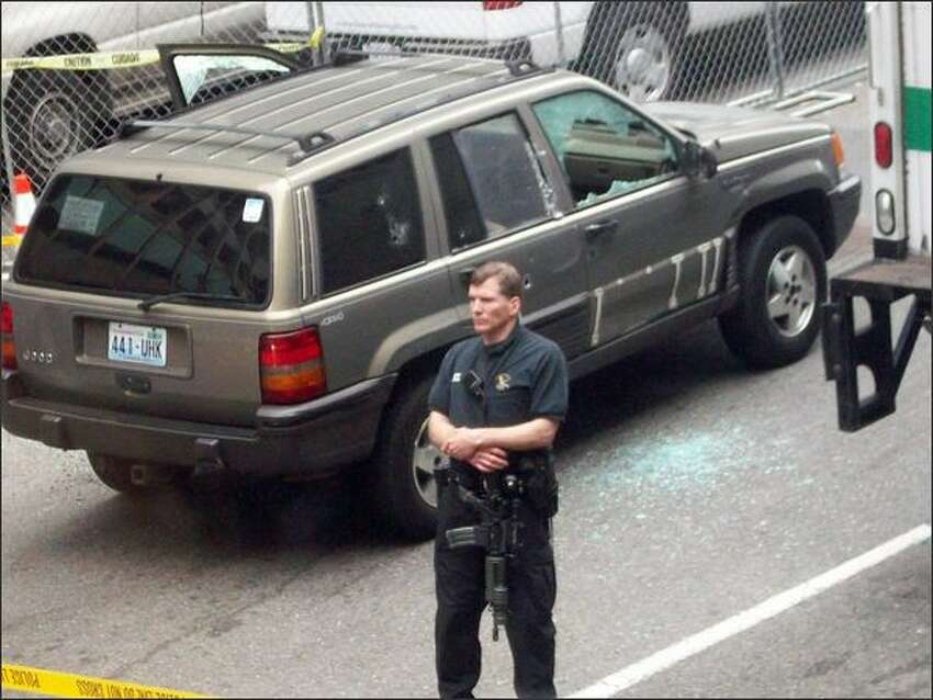 Police secure the scene where a suspect was shot in this Jeep on Tuesday morning. (Photo by Michele DeMaris)