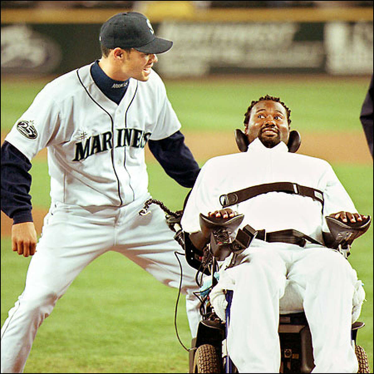 Former University of Washington football player Curtis Williams jokes with Mariner Charles Gipson before a game at Safeco Field on April 24. Williams, who threw out the first pitch prior to the game against Anaheim, became paralyzed after being injured during a game at Stanford on Oct. 28, 2000. Williams died in Clovis, Calif., on May 6.