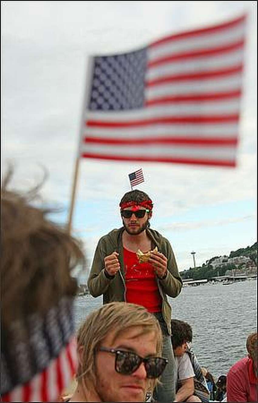 Josh Archer, of Capitol Hill, middle with sandwich, hangs with friends and before the fireworks show at Gas Works Park in Seattle on the Fourth of July.