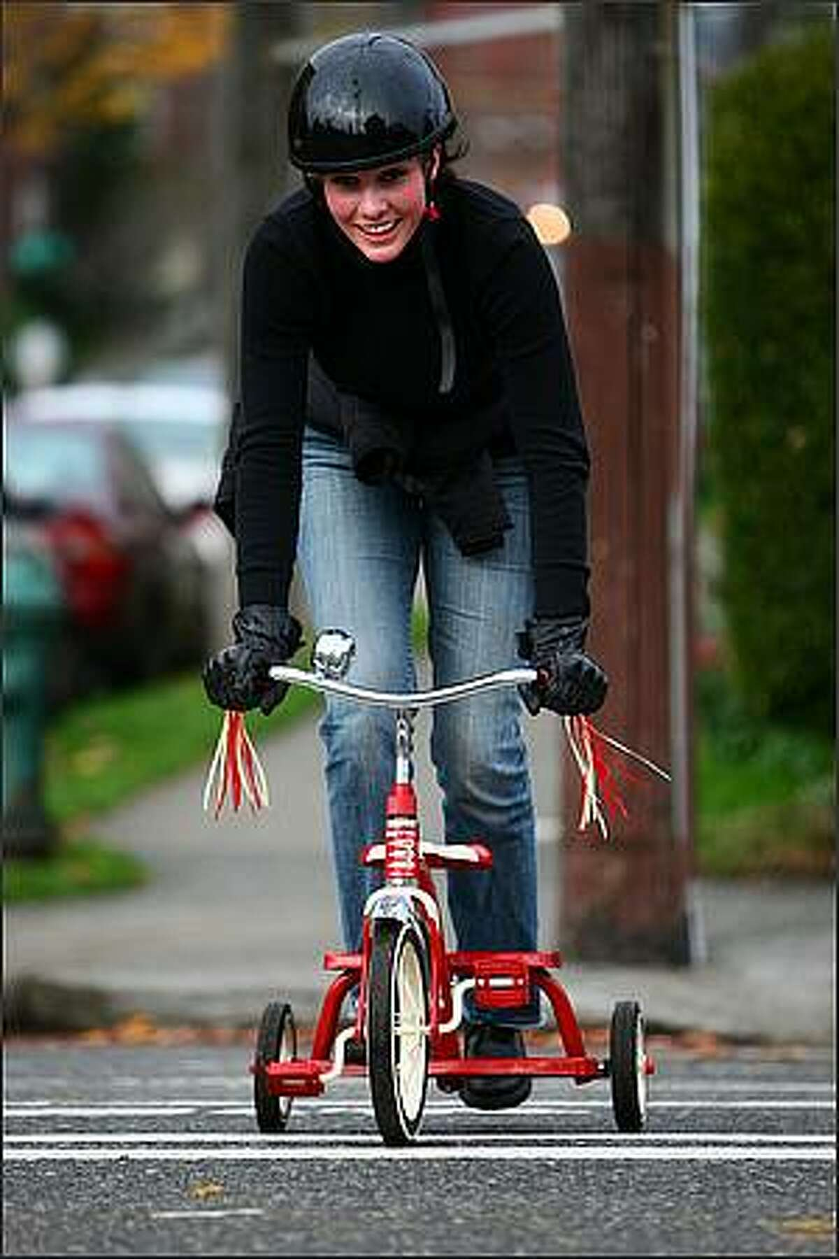 Tricycle rider Shaney Clemmons approaches the finish line, the door of the Streamline Tavern in Lower Queen Anne, during the Queen Anne Tricycle Race on Sunday. Helmets and safety gear were encouraged for participants who screamed down some of Queen Anne's steep hills.