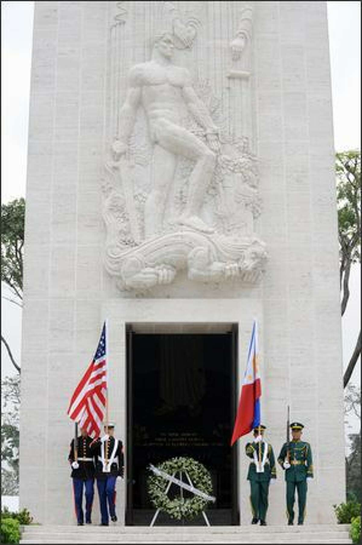 Philippine and U.S. military honor guards carry the flags of the Philippines and the U.S. at the war memorial at Manila American Cemetery during the annual Veterans' Day ceremony in Manila on Tuesday. The Veterans' Day mark the end of hosilities of World War I when the Armistice was signed November 11 -- the eleventh hour of the eleventh day of the eleventh month in 1918.