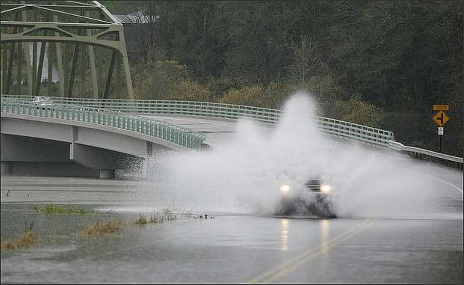 After the road was closed, a truck is obscured as it crosses NE Tolt Hill Rd. in Carnation, Wash. The Snoqualmie River is one of the several area rivers at flood level. Photo: Dan DeLong, Seattle Post-Intelligencer