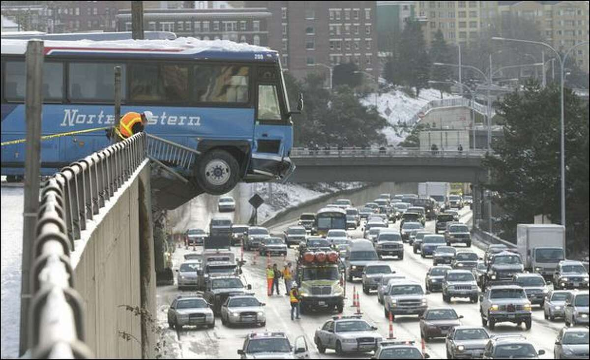 Two buses slid down the snow- and ice-covered East Thomas Street, hitting each other and then careening on through a guardrail on Melrose Avenue East, and finally stopping, 20 to 30 feet above Interstate 5.