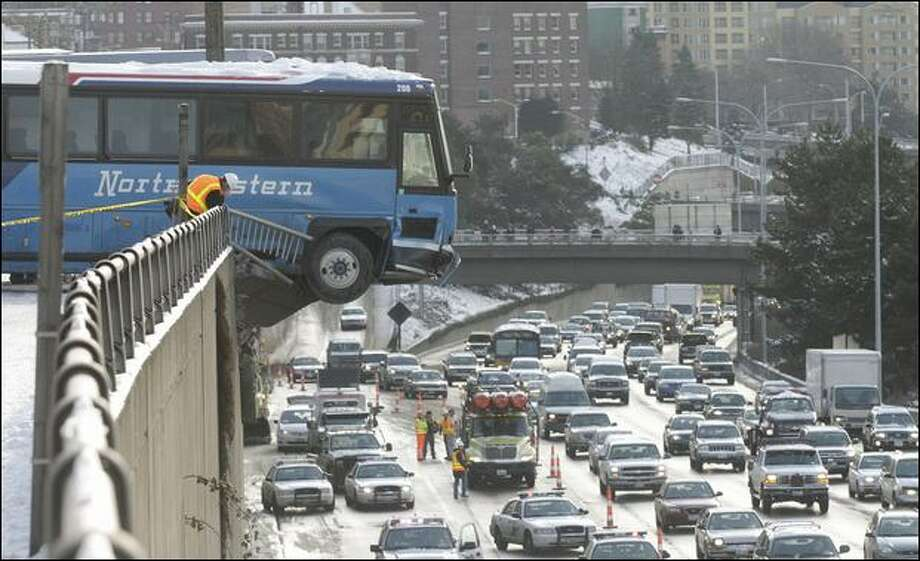 Two buses slid down the snow- and ice-covered East Thomas Street, hitting each other and then careening on through a guardrail on Melrose Avenue East, and finally stopping, 20 to 30 feet above Interstate 5. Photo: Dan DeLong/Seattle Post-Intelligencer
