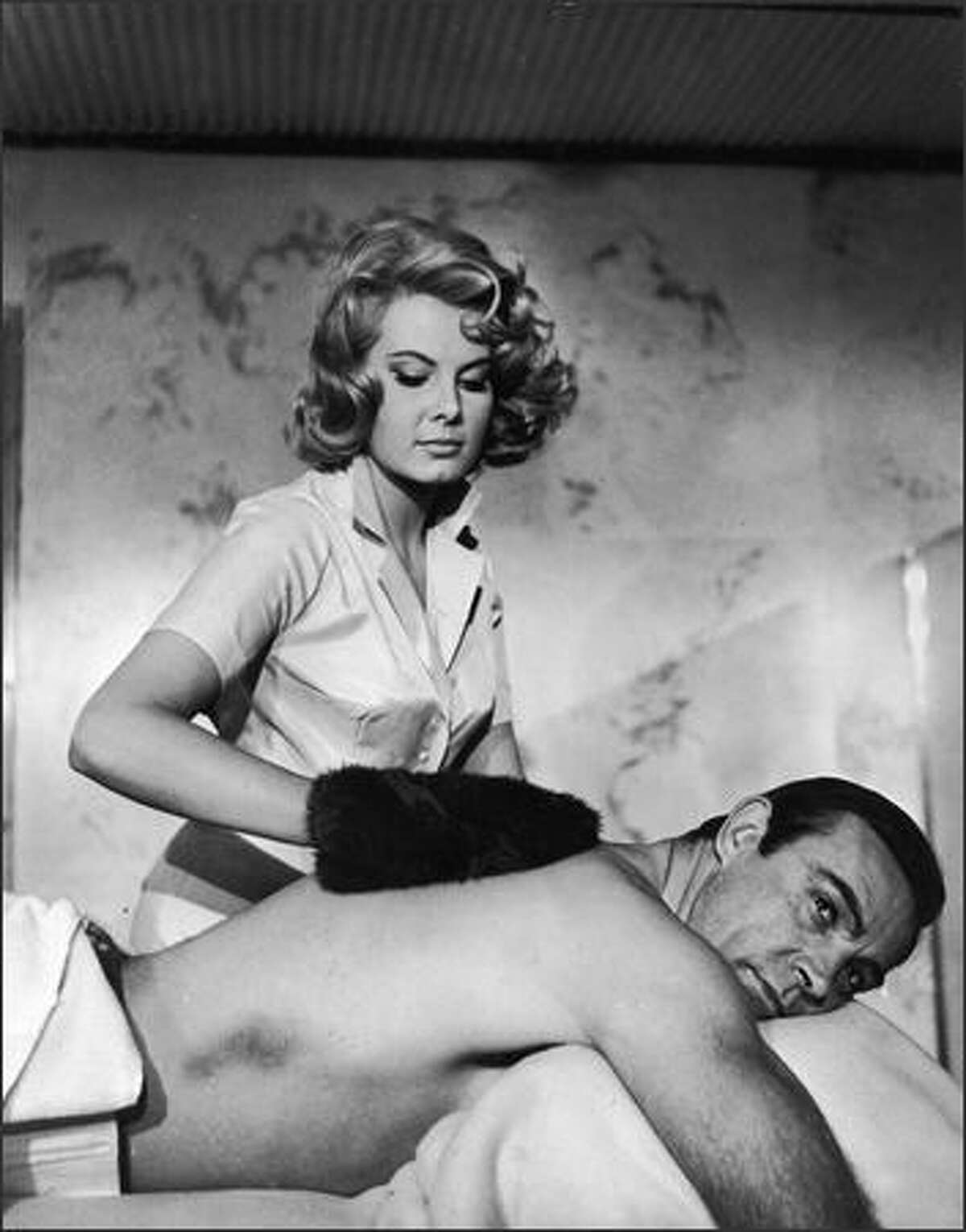 Sean Connery gets a massage from Molly Peters in a still from the James Bond film,