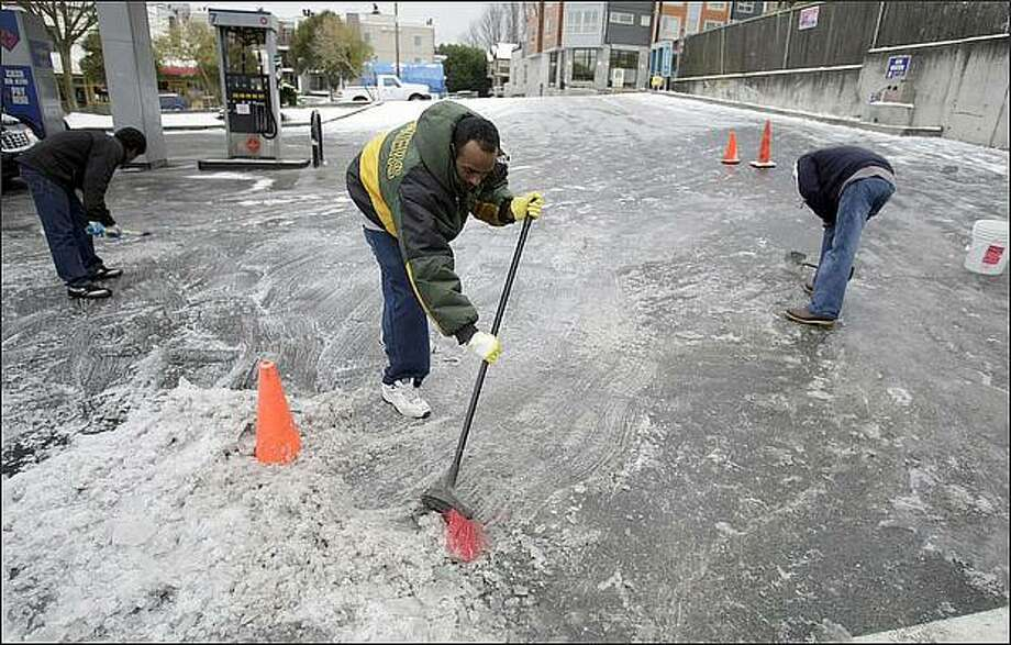 Teages Kelati, center, helps his friend, Binyam Tekie, right, the manger of this gas station on West Dravus Street in Magnolia, to break up and shovel ice. On the left is friend Goitom Medhin. Photo: Meryl Schenker/Seattle Post-Intelligencer