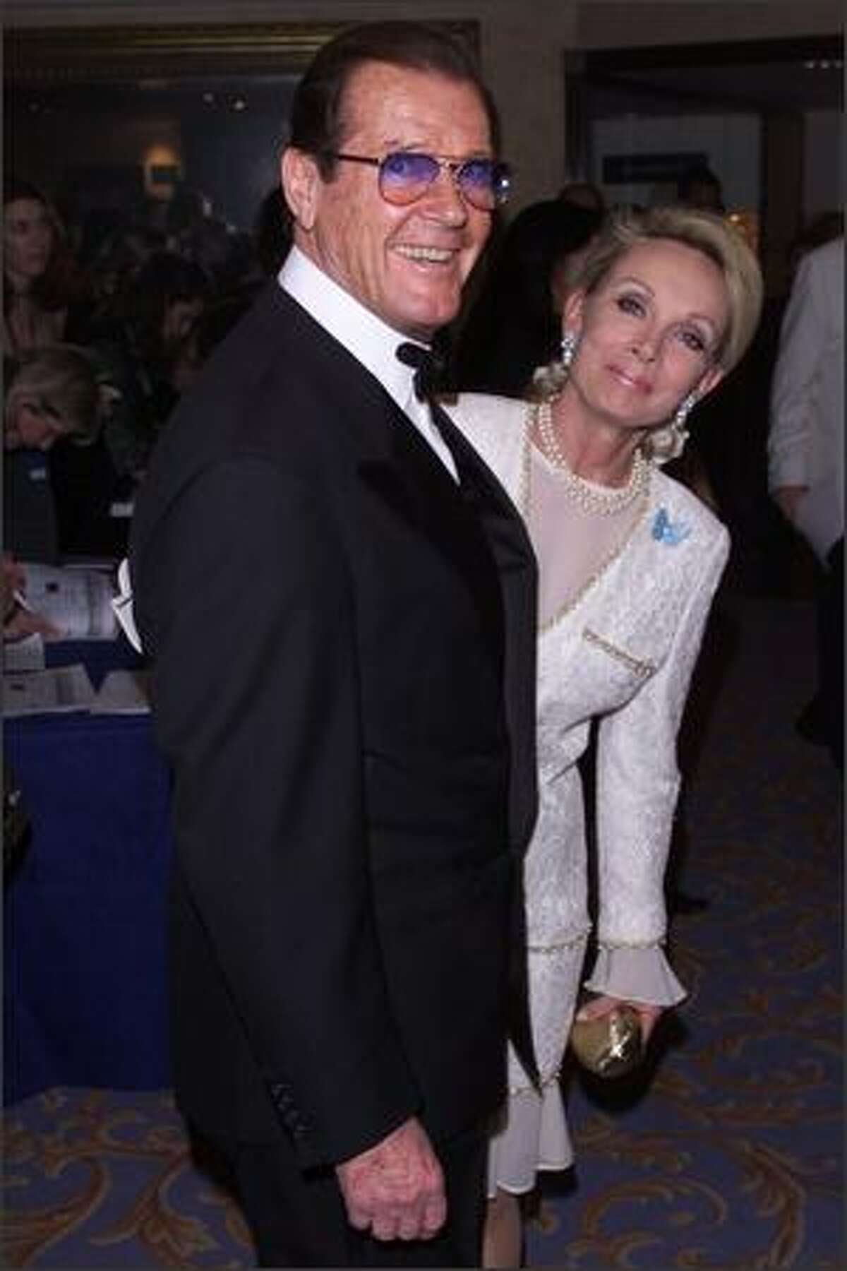 British actor Roger Moore and his girlfriend at Muhammad Ali's 59th birthday celebration at the Hilton Hotel, Park Lane, London on January 17th 2001.