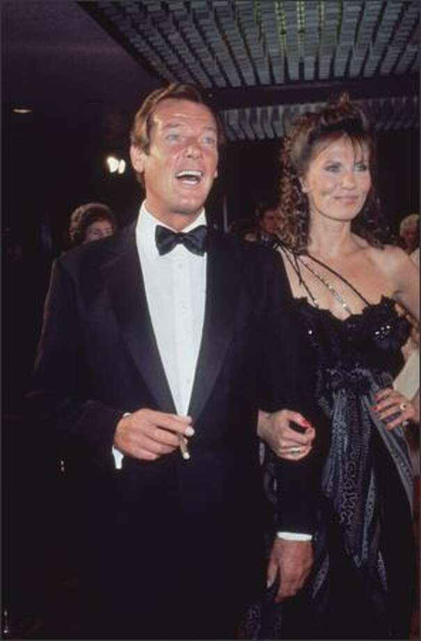 1983: A laughing Roger Moore arrives at the premiere of the James Bond film 'Octopussy' with his co-star, Swedish actress Maud Adams. Photo: Getty Images