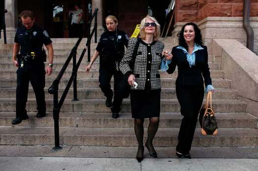 Miss Bexar County Organization, Inc., Executive Director Caroline Flores (left) and President Linda Woods leave the Bexar County Courthouse together after a jury found that the organization had breached its contract with Domonique Ramirez. Judge Barbara Hanson Nellermoe ordered the Miss San Antonio crown returned to Ramirez on Thursday, March 24, 2011. The women were escorted by Bexar County Sheriff's Deputies Joe Gaska (far left) and Chris McLaurin after Woods stated she had received death threats. Photo: Lisa Krantz/Express-News / SAN ANTONIO EXPRESS-NEWS