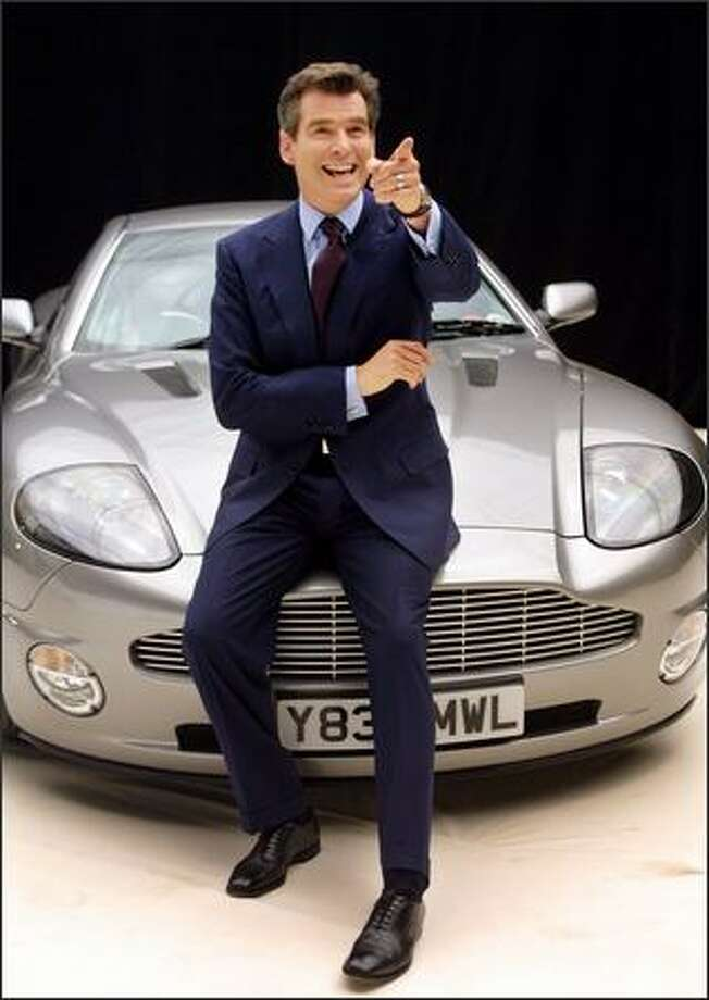 Pierce Brosnan poses seated on an Aston Martin during a photocall at Pinewood Studios on January 11, 2002. Photo: Getty Images