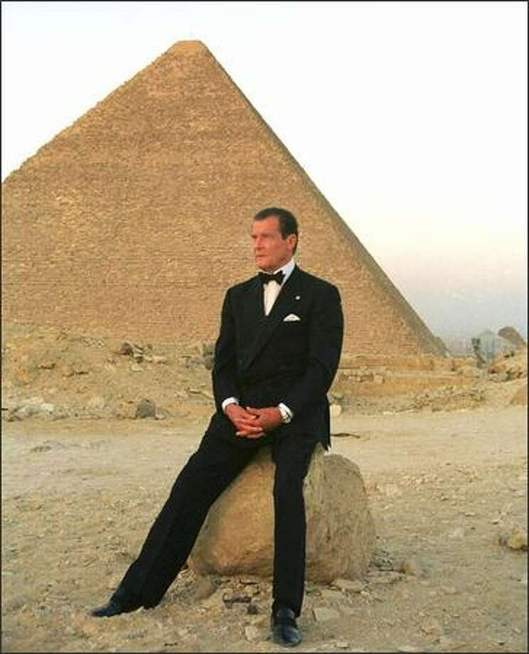 Former secret agent 007 Roger Moore poses in front of Cheops, the largest of Egypt's three Pyramids on the Giza plateau south of Cairo on July 2, 1999. Photo: Getty Images