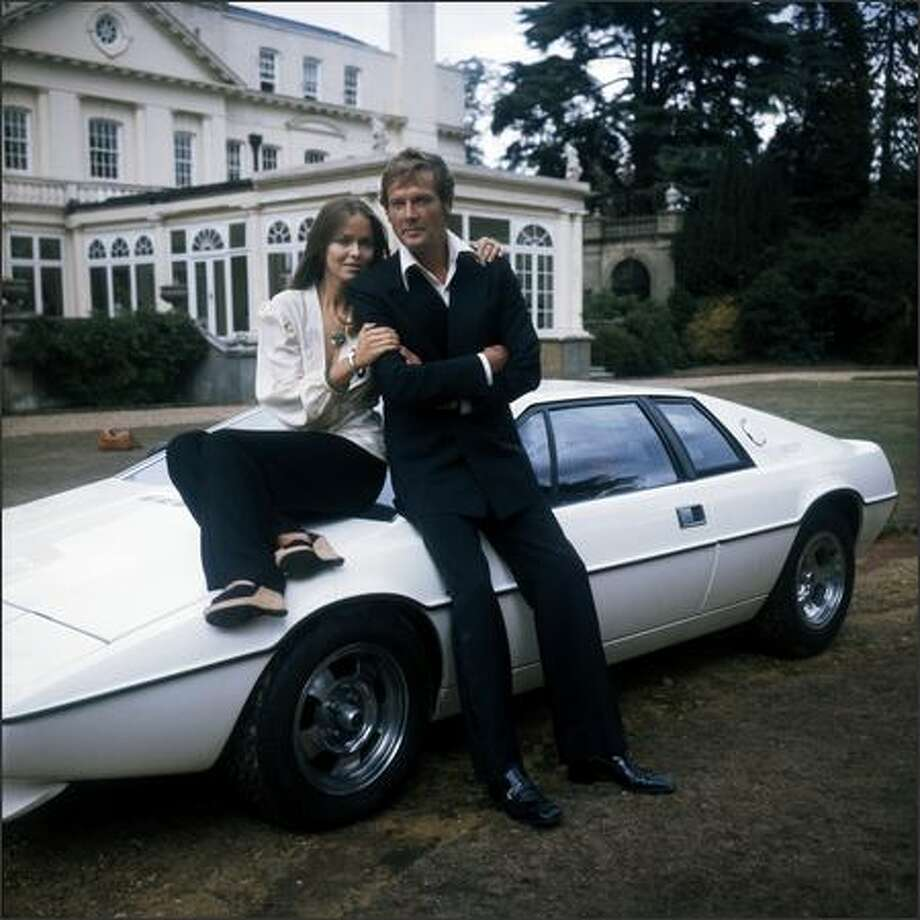 1977: Barbara Bach and Roger Moore, stars of the James Bond film 'The Spy Who Loved Me' leaning on the now-famous 'amphibious' Lotus Esprit. Photo: Getty Images