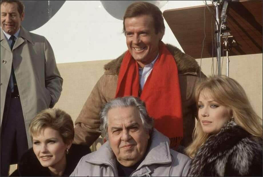 1985: From left to right, Fiona Fullerton, producer Albert 'Cubby' Broccoli (1909-1996) and Tanya Roberts, and behind them, a grinning Roger Moore, during the making of the James Bond film 'A View to a Kill' at Pinewood Studios. Photo: Getty Images