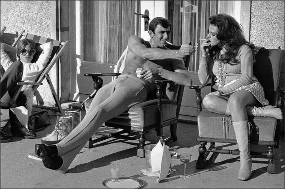 October 22, 1968: Stripped to the waist, Australian actor George Lazenby offers co-star Helena Ronee a light, while filming the new James Bond film 'On Her Majesty's Secret Service' in the Swiss Alps. Photo: Getty Images