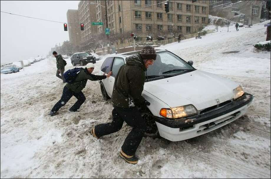 Russell Potier, in front, helps a stuck motorist in Capitol Hill on Sunday. Photo: Mike Kane/Seattle Post-Intelligencer