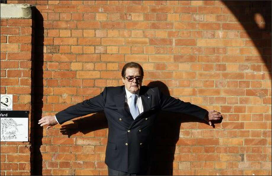British actor Roger Moore poses for a photograph at a 'James Bond photocall' at Bletchley Park in Mi