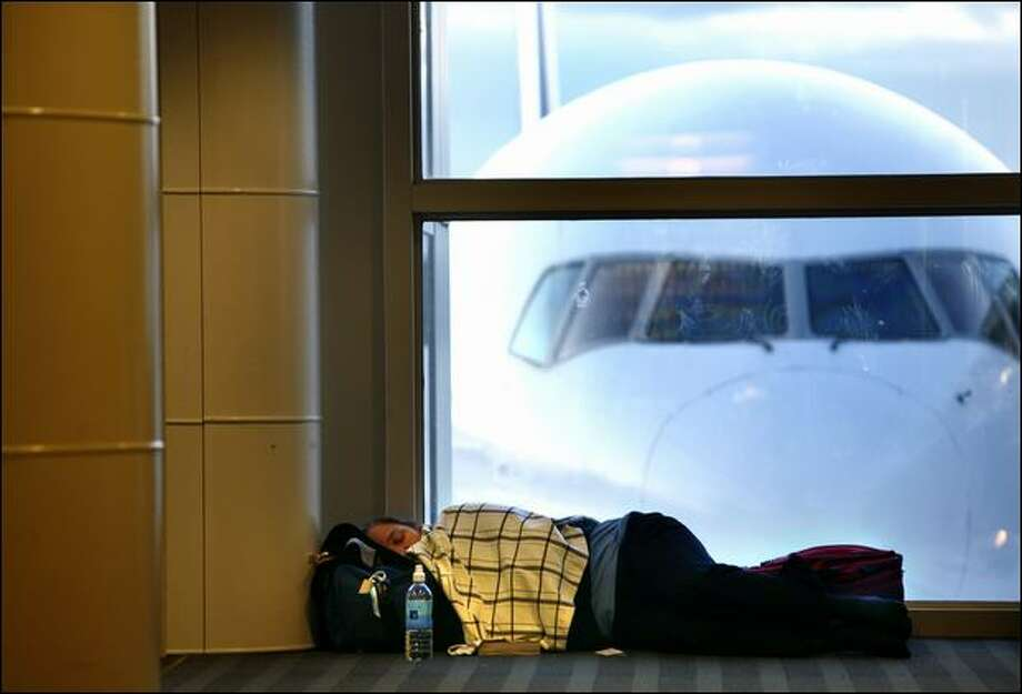 A passenger sleeps on the floor, waiting for a flight on Monday at Sea-Tac International Airport, a day after a snowstorm caused numerous flight cancellations, stranding holiday travelers. Photo: Joshua Trujillo/Seattle Post-Intelligencer