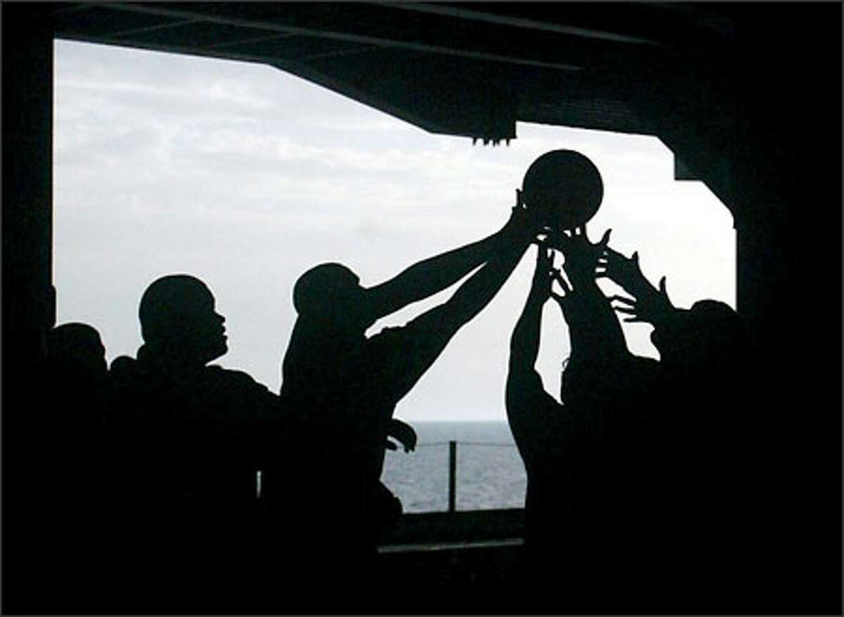 Persian Gulf. Sailors on board the Lincoln grab for a loose ball during basketball game Monday as they enjoyed a