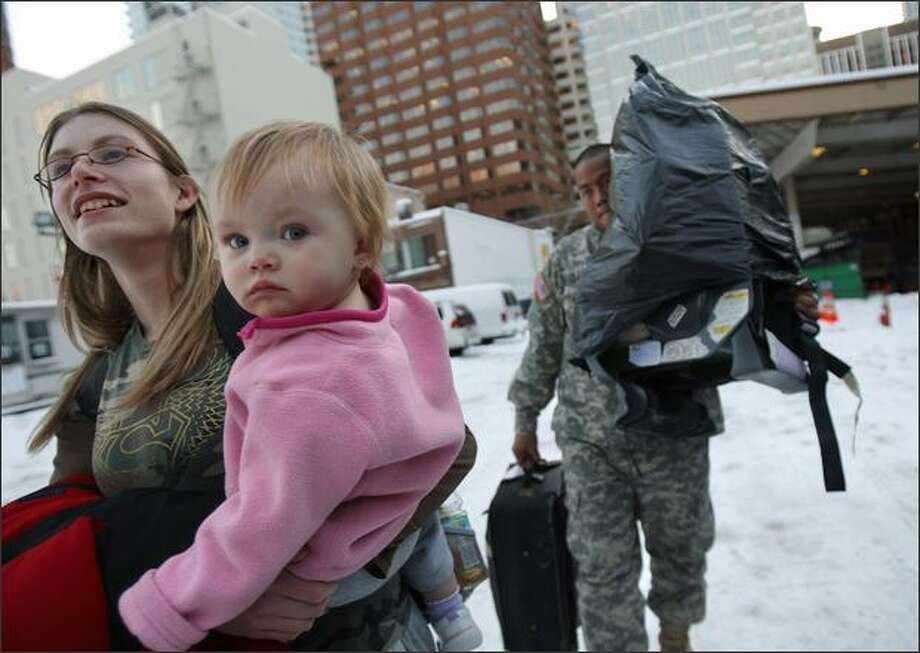 Nicolette Shown and her 1-year-old daughter Baylee Rae get a helping hand from Pvt. Jesse De La Cruz, whom they met while waiting for a bus at the Greyhound station in Seattle on Monday. Shown was traveling to visit family in Portland but became stranded at the Seattle station after already having spent a day in Spokane. Her father ended up driving from Portland to get her. De La Cruz continued to wait for his bus. Photo: Andy Rogers/Seattle Post-Intelligencer