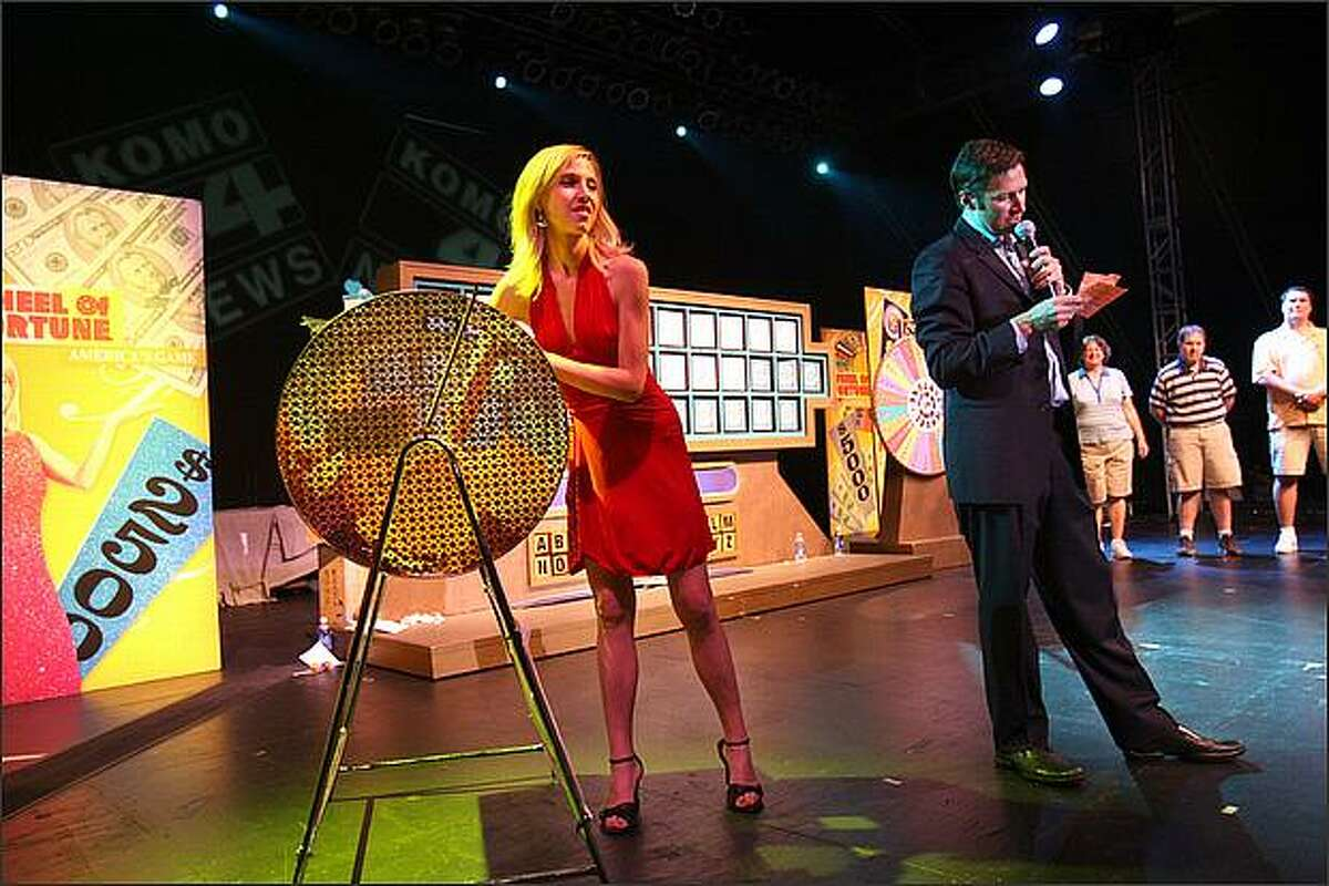 Nervous anticipation prevails over the audience as Wheel of Fortune hosts Heidi Jackson grabs a slip of paper and Marty Lublin reads the name on it.