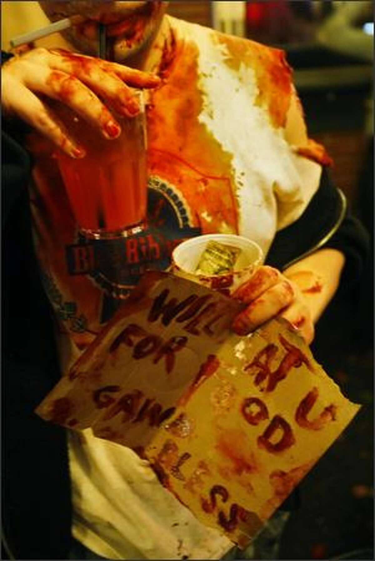 """A """"zombie"""" holds a sign that says """"will eat u for food, gawd bless."""""""