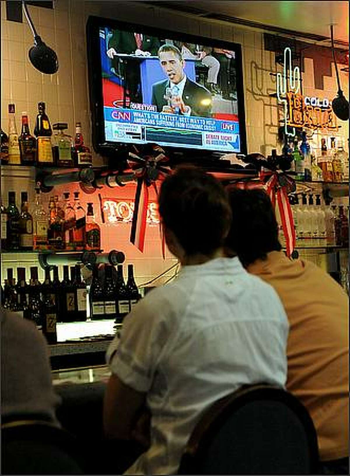 Patrons watch Democratic presidential candidate Sen. Barack Obama speaking during a presidential debate Tuesday, Oct. 7, 2008 at Tom's Tavern in Phoenix. (AP Photo/Matt York)
