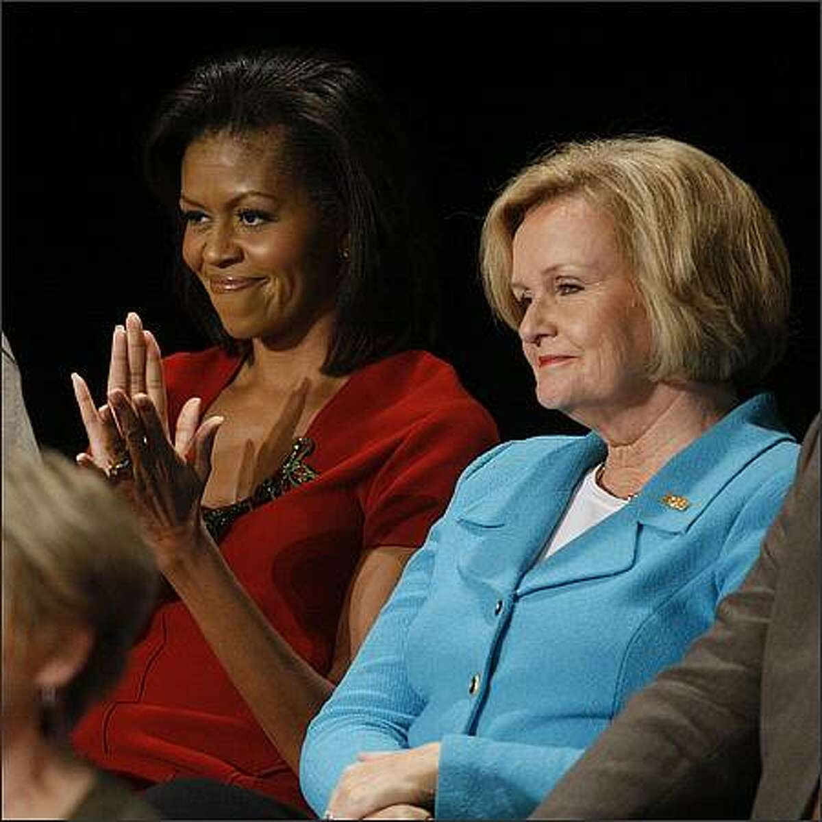 Michelle Obama, wife of Democratic presidential candidate Sen. Barack Obama, left, accompanied by Sen. Claire McCaskill , D-Mo., applauds prior to the start of a townhall-style presidential debate at Belmont University in Nashville, Tenn., Tuesday, Oct. 7, 2008. (AP Photo/Pool, Charles Dharapak)
