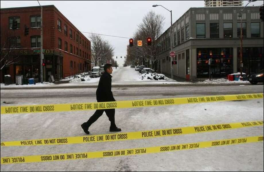 A pedestrian crosses Bell Street, the bottom part of which has been closed with police tape because of slippery conditions. Photo: Mike Kane/Seattle Post-intelligencer