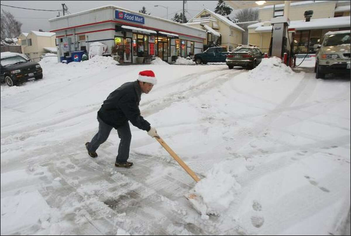 James Kim, of Federal Way, shovels snow with a homemade shovel in front of his gas station in Seattle's Magnolia neighborhood on Wednesday. Kim made the shovel out of a wooden board and piece of plywood when he found that all area stores had sold out of shovels.