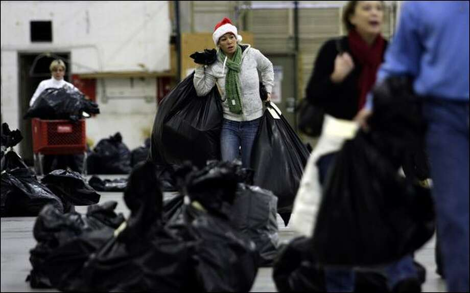 Volunteer Stacy Swanson, center, of Seattle carries bags of gift items to be sorted for delivery to needy families by the Forgotten Children's Fund in Seattle. Snow has delayed deliveries intended for Christmas Day until Sunday, but parents with transportation can pick up the gifts. Photo: Andy Rogers/Seattle Post-Intelligencer