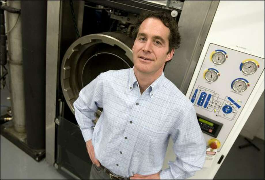 Blue Sky owner Mark Callaghan stands at one of the dry-cleaning machines, which use carbon dioxide instead of chemicals. Photo: Brad Vest/Seattle Post-Intelligencer